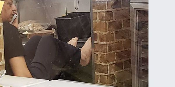 Subway employee caught in photo with bare feet on counter near food prep area
