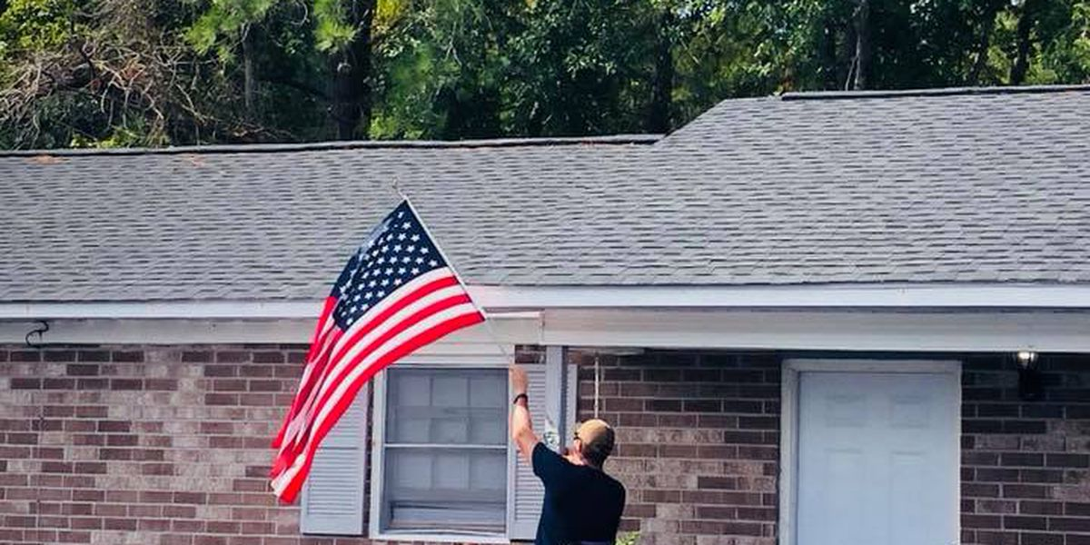 Powerful image shows Army vet hanging American flag over floodwaters