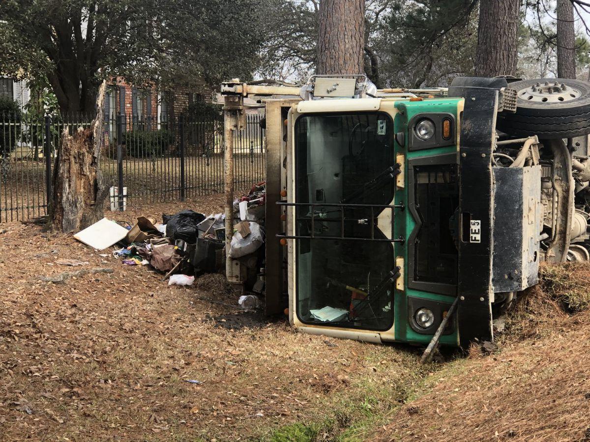 Trash truck overturns to avoid hitting car